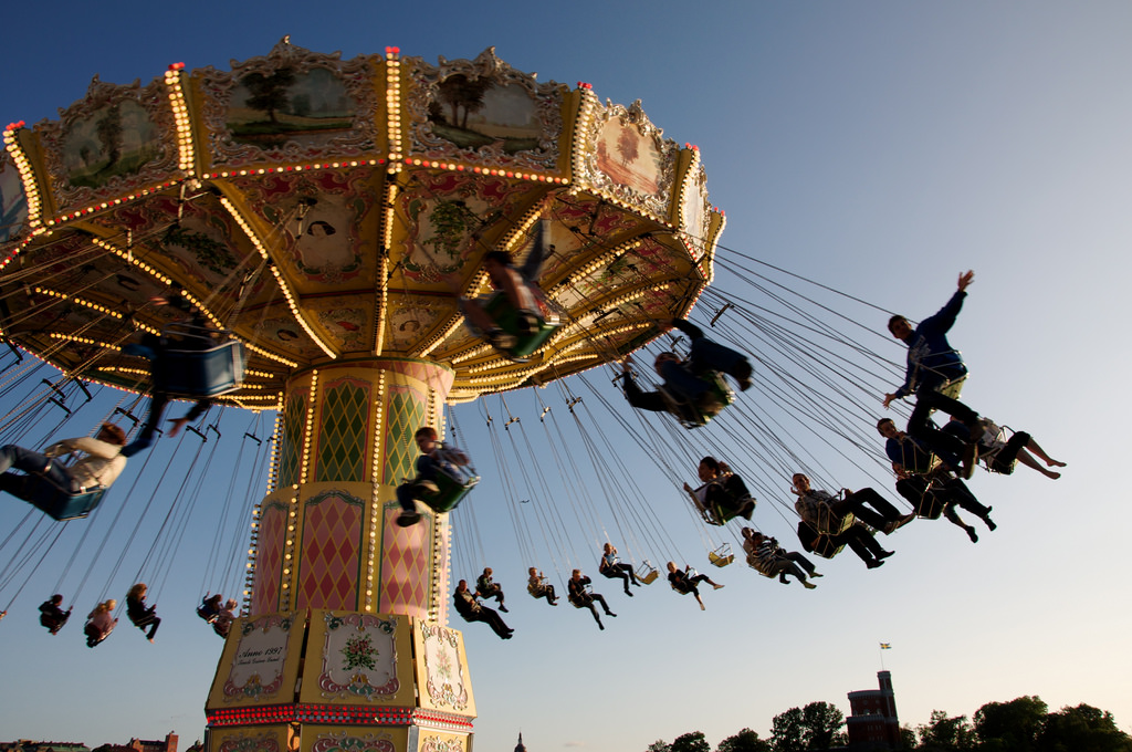 Adults and Kids Enjoying on swing Carousel at the Zero Gravity Amusement Park Ride during the day